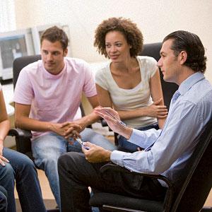 Foto: Gruppe junger Personen beim Diskutieren, angeleitet durch einen Supervisor